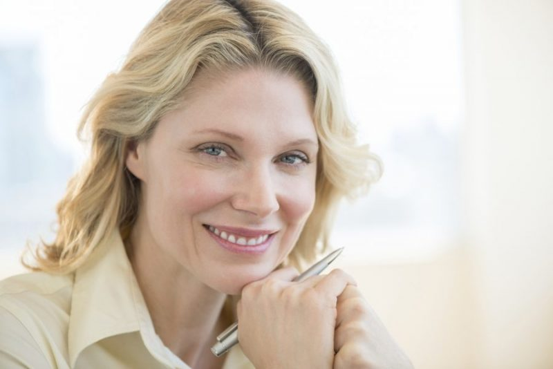 Businesswoman With Hand On Chin Smiling In Office